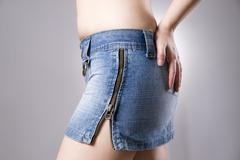 Woman in jeans skirt close up. Beautiful female hips and buttocks - stock photo