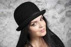 Portrait of a beautiful young woman in a bowler hat - stock photo