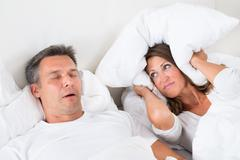 Woman Covering Her Ears With Pillow While Man Snoring Kuvituskuvat