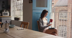 Morning coffee for mixed race woman happy at home in pajamas Stock Footage