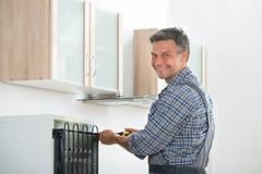 Portrait of happy mature handyman repairing refrigerator at home Stock Photos