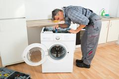 Full length of handyman checking washing machine with flashlight in kitchen Stock Photos