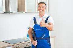Portrait of happy male janitor gesturing thumbs up in kitchen - stock photo