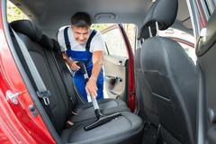 Mature handyman vacuuming car back seat with vacuum cleaner Stock Photos
