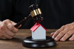 Cropped image of judge holding gavel on house model at desk Stock Photos