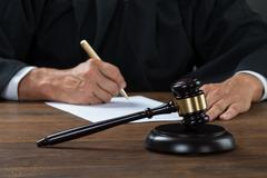 Midsection of judge writing on paper at table in courtroom Stock Photos