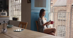 Morning coffee for mixed race woman happy at home in pajamas using smart phone - stock footage