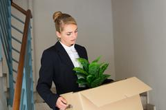 Sad young businesswoman carrying her belongings in cardboard box at office Stock Photos