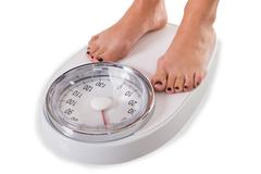 Low section of woman standing on weighing scale over white background Stock Photos