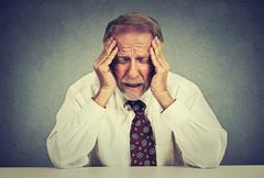 Stressed hopeless elderly business man in depression sitting at the office ta - stock photo