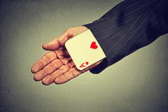 cropped image senior man hand pulling out a hidden ace from the sleeve - stock photo