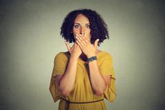Woman covering closed mouth with hands. Speak no evil concept Stock Photos