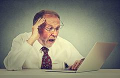 Closeup portrait anxious senior man looking at laptop screen seeing bad news  - stock photo
