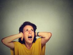 annoyed unhappy stressed woman covering her ears, looking up, screaming - stock photo