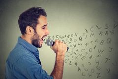 Young man singing in microphone with alphabet letters coming out of his mouth Stock Photos