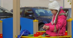 Little Blonde Girl With Braid is Playing Cook Toy Plates on a Table with Sand Stock Footage