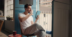 Happy man at home in pajamas calling friends using digital tablet app Stock Footage