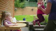 4K Mother putting toddler twins into high chairs, in the backyard at home - stock footage