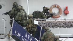 Anti terrorist gas masked Portuguese soldiers take control of abducted boat Stock Footage