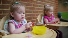 4K Cute toddler twins in high chairs eating snacks Stock Footage
