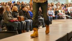 Young guy model walking on catwalk on the fashion clothes show Stock Footage