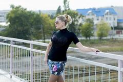 the sexy girl in a miniskirt on the bridge, railway tracks - stock photo