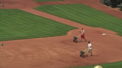 Men preparing baseball diamond for upcoming game Stock Footage