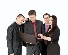 Four businessman standing at the table for a laptop and conduct business talk Stock Photos