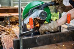 Industrial worker cutting metal with many sharp sparks working on compound mi Stock Photos