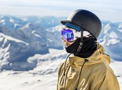 Portrait of young snowboarder in helmet and sunglass mask at the ski resort E - stock photo