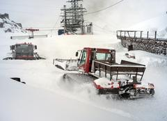 Stock Photo of Snowcat in motion in snowfall on slope in the mountains at skiing resort Elbr