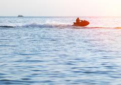 Silhouette of a man and young girl in motion on jetski on the sea Stock Photos