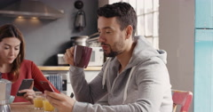 Couple using smart phone devices eating breakfast at home drinking coffee - stock footage