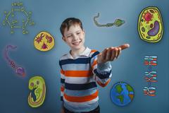 Boy smiling and holding in the palm of icons biology education f Stock Photos