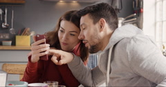 Happy couple at home using smart phone together - stock footage