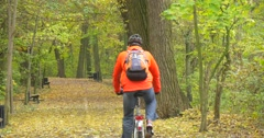 Man in Orange Jacket And Safety Bicycle Helmet Man with Backpack is Riding the Stock Footage
