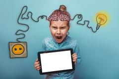 Teenage girl holding a tablet and angry shouts charging cord plu - stock photo