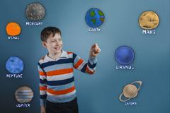 Teenage boy laughing and holding a finger of the planet of the s - stock photo
