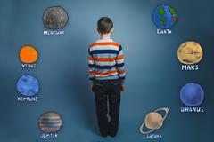 Teenage boy standing with his back planets of the solar system a - stock photo