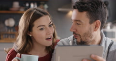 Happy couple using digital tablet at home spending time together Stock Footage