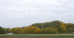 Stock Video Footage of Green And Yellow Trees on a Horizon at Opposite Bank of the Lake Landscape Pond