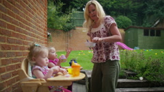 4K Cute toddler twins in high chairs eating snacks - stock footage