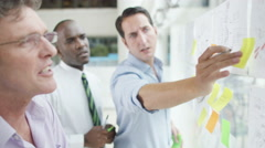 4K Male creative design team brainstorming for ideas with sticky notes - stock footage