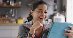 Happy mixed race woman laughing while watching funny internet video using - stock footage