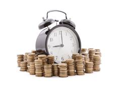 Time is money. Alarm clock with stacks of coins. Clipping path included. Stock Photos