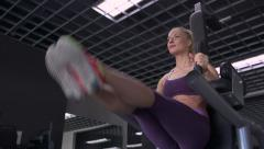 Young woman in sportswear exercising abdominals in gym. Dolly shot. - stock footage