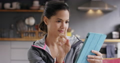 Pretty mixed race woman using touch screen digital tablet at home in kitchen Stock Footage