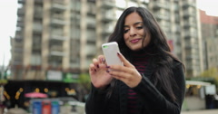 Young Indian woman in city texting cell phone - stock footage