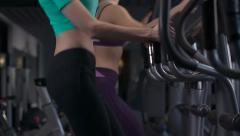 Two young women on elliptical treadmill trainer in fitness gym exercising. Arkistovideo