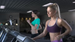 Two attractive girls running on the treadmill in the gym. Dolly shot. - stock footage